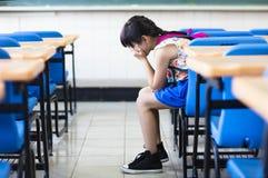 Trauriges Mädchen, das im Klassenzimmer sitzt stockfoto