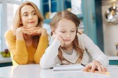 Trauriges Mädchen, das mit ihrem Notizbuch sitzt Lizenzfreie Stockfotos