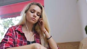 Trauriges Mädchen, das Musik auf Mobiltelefon im Café hört stock video