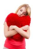 Trauriges Mädchen der Frau, das rotes Herzliebessymbol umarmt Lizenzfreie Stockfotos