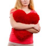 Trauriges Mädchen der Frau, das rotes Herzliebessymbol umarmt Stockfotos