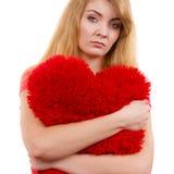 Trauriges Mädchen der Frau, das rotes Herzliebessymbol umarmt Stockbild