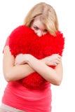 Trauriges Mädchen der Frau, das rotes Herzliebessymbol umarmt Stockfotografie