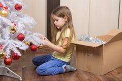 Trauriges Mädchen entfernt einen Weihnachtsbaum mit Spielwaren Stockbild