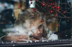 Trauriges Mädchen hinter Fenster und Katze Stockfotos