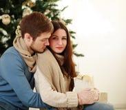Trauriges Mädchen mit einem Geschenk in der Umarmung ihres Freundes Stockfoto