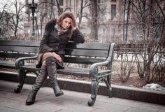 Trauriges Mädchen sitzt auf der Bank Stockfotos