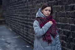 Trauriges Mädchen steht nahe einer Backsteinmauer im Jackenhut und -schal stockfotos
