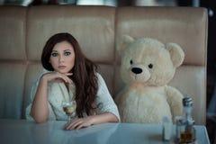 Trauriges Mädchen am Tisch mit einem Spielzeugbären stockbilder