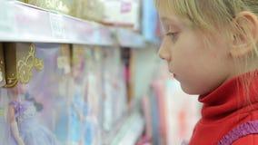 Trauriges Mädchen, welches die Puppen im Paket betrachtet stock footage