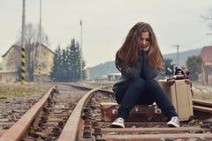 Trauriges Mädchen, das auf altem Koffer auf Schienen sitzt Lizenzfreies Stockbild