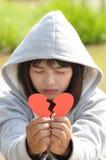 Trauriges Mädchen, das betet, um von defektem Herzen zu versöhnen Lizenzfreie Stockfotos