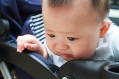 Trauriges nettes asiatisches Baby, das heraus vom Babyauto aufpasst Stockfoto