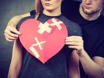 Trauriges Paar hält defektes Herz Stockbilder