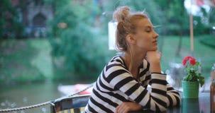 Trauriges recht kaukasisches Mädchen, das am Freiencafé sitzt und auf jemand wartet stock video footage