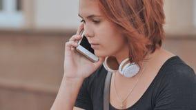 Trauriges rothaariges Mädchen in den Kopfhörern wählt eine Nummer am Telefon und wartet auf eine Antwort stock footage