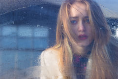 Trauriges schönes seksalnaya recht trauriges einsames Mädchen hinter nassem Glas mit großen traurigen Augen in einem Mantel stockfotografie