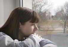 Trauriges schauendes Fenster der netten jungen brunette Frau, Nahaufnahme stockfotos