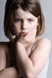 Trauriges schauendes Kind gegen einen grauen Hintergrund Lizenzfreie Stockfotos