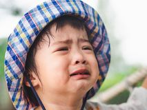 Trauriges schreiendes Gesicht des kleinen Mädchens auf bokeh Hintergrund mit Weinlese fil stockfotografie