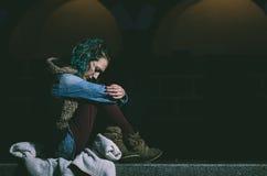 Trauriges Sitzen der jungen Frau allein während es ` s Regnen stockfoto