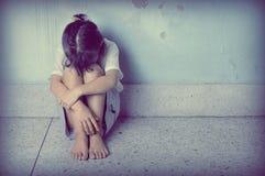 Trauriges und deprimiertes kleines Mädchen, das nahe der Wand sitzt Lizenzfreie Stockfotos
