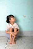 Trauriges und deprimiertes kleines Mädchen, das nahe der Wand sitzt Stockfoto