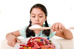 Trauriges und verletzbares hispanisches weibliches Kind, das voll Teller der Süßigkeit und der gummies halten Zuckerlöffel im fal Stockfotos