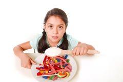 Trauriges und verletzbares hispanisches weibliches Kind, das voll Teller der Süßigkeit und der gummies halten Zuckerlöffel im fal Lizenzfreies Stockbild
