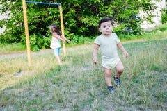 Trauriges wenig lateinisches Jungengehen und ein kleines Mädchen, das Sport im Hintergrund tut Lizenzfreie Stockfotos
