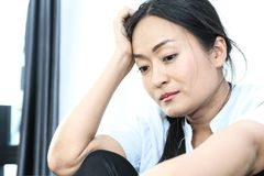 Traurigkeits-Asiatinnen halten eine Pistole lizenzfreies stockbild