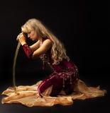 Traurigkeitsfrau im arabischen Kostüm sitzen mit Säbel Stockfotografie