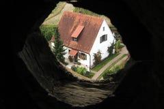 Casa vista a través del agujero en pared Imágenes de archivo libres de regalías