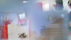A través del escaparate de una floristería, usted puede ver muchas diversos flores y ramos el tienda-estudio entero de la flor almacen de video