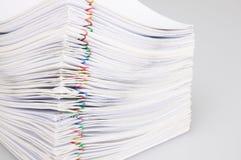Trava överbelastningsskrivbordsarbete med den färgrika paperclipen på vit bakgrund Arkivfoton