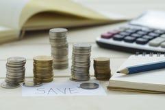 Trava myntpengar med grafbankrörelseconceptn och spara ordet på papper Arkivbilder