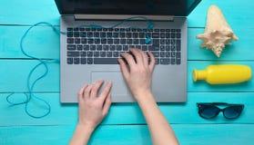 Travail à distance pour un ordinateur portable dans une station balnéaire Les mains femelles dactylographient le texte sur le cla Image libre de droits