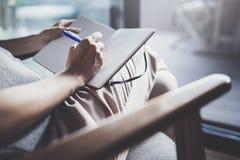 travail à domicile de concept Jeunes écriture de femme d'affaires et notes de prise tandis que détendez la séance dans la chaise  images libres de droits