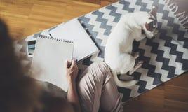 travail à domicile de concept Jeunes écriture de femme d'affaires et notes de prise tandis que détendez la séance dans la chaise  photo stock