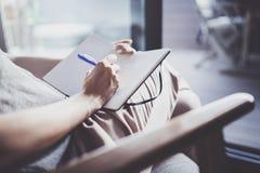 travail à domicile de concept Jeunes écriture de femme d'affaires et notes de prise tandis que détendez la séance dans la chaise  photo libre de droits