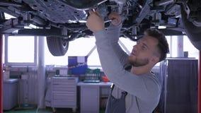Travail à l'atelier, mécanicien beau avec la clé fonctionnant sous le fond de la voiture à la station service de réparation clips vidéos