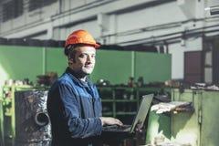 Travail à l'usine avec un ordinateur portable à disposition sur le fond de images stock