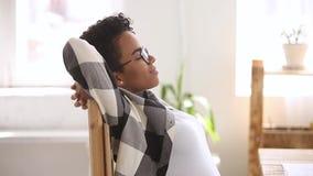 Travail accompli de femme africaine de vue de profil étirant le repos sur la chaise banque de vidéos