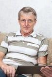 Travail adulte mûr avec la tablette au sofa domestique Photos libres de droits