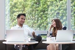 Travail asiatique d'ordinateur portable d'utilisation de deux collègues ayant ensemble le café dans l'af image libre de droits