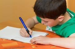 Travail d'écriture de garçon d'école en cahier de travail Images libres de droits
