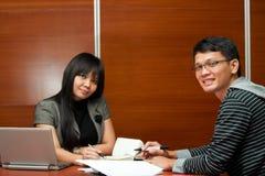 Travail d'équipe asiatique heureux d'affaires lors du contact photographie stock