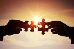 Travail d'équipe, association et concept de coopération Silhouettes de deux mains joignant deux morceaux de puzzle ensemble image stock