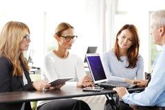 Travail d'équipe avec l'ordinateur portable au bureau Photos stock
