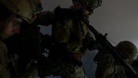 Travail d'équipe des escaliers descendants spéciaux d'unité militaire pendant une intervention opérationnelle armée dans le bâtim banque de vidéos